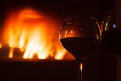 Vetro di vino rosso in fonte del fuoco di ceppo Fotografia Stock
