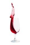 Vetro di vino rosso su che versa, spruzzata isolata su bianco Fotografia Stock