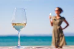 Vetro di vino rosso sulla tavola sopra il backgound di Lazise della giovane donna fotografie stock libere da diritti