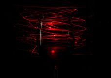 Vetro di vino rosso sulle bande rosse del fondo di una luce dell'estratto su fondo nero Immagine Stock