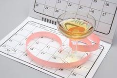 Vetro di vino sul calendario fotografia stock libera da diritti