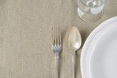 Vetro di vino vuoto d'annata bianco del cucchiaio della forcella dell'argento del semicerchio dei piatti su tessuto di tela beige Immagini Stock