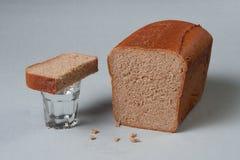 Vetro di vodka, di pane e delle briciole Fotografia Stock