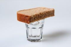 Vetro di vodka e di un pezzo di pane Fotografie Stock