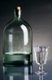 Vetro di vodka e di una bottiglia Fotografia Stock