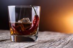 Vetro di whiskey con ghiaccio ed il peperoncino rosso Fotografia Stock Libera da Diritti
