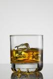 Vetro di whiskey con ghiaccio su fondo bianco Fotografia Stock Libera da Diritti