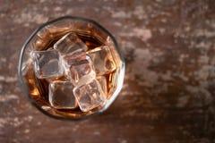 Vetro di whiskey con ghiaccio su fondo nero Fotografia Stock