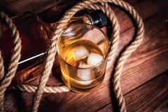 Vetro di whiskey con ghiaccio, una bottiglia di singoli whiskey di malto Fotografie Stock Libere da Diritti