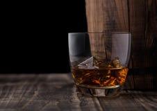 Vetro di whiskey con i cubetti di ghiaccio accanto al barilotto di legno Bevanda del brandy del cognac fotografia stock libera da diritti