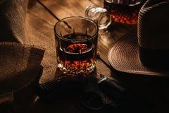 Vetro di whiskey, del revolver e del cappello Fotografia Stock