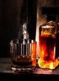 Vetro di whiskey scozzese e di una bottiglia su vecchio fondo di legno. O immagini stock