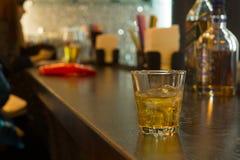 Vetro di whiskey su ghiaccio su un contatore della barra Fotografia Stock Libera da Diritti