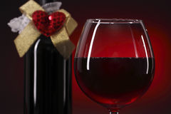 Vetro e bottiglia del vino rosso con cuore Fotografia Stock