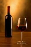 Vetro e bottiglia del vino rosso sulla tavola di legno e sul fondo dorato Fotografia Stock Libera da Diritti