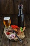 Vetro e bottiglia di birra con le salsiccie, i pomodori ciliegia e la cipolla Fotografia Stock Libera da Diritti