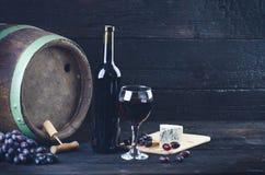 Vetro e bottiglia di vino su un barilotto di legno Fondo di legno bruciato e nero annata Copyspace per un testo Uva e vite verde Fotografie Stock