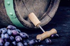 Vetro e bottiglia di vino su un barilotto di legno Fondo di legno bruciato e nero annata Copyspace per un testo Uva e vite verde Immagine Stock