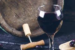 Vetro e bottiglia di vino su un barilotto di legno Fondo di legno bruciato e nero annata Copyspace per un testo Uva e vite verde Immagini Stock Libere da Diritti