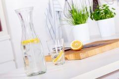 Vetro e carafe con limonata su un contatore di cucina fotografie stock