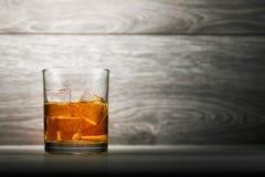 Vetro e ghiaccio del whiskey su fondo di legno Immagine Stock Libera da Diritti