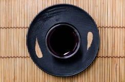 Vetro e piattino su un sottobicchiere di legno nero Immagine Stock Libera da Diritti