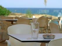 Vetro e portacenere di Emty sulla tavola in un ristorante vicino alla spiaggia fotografia stock libera da diritti