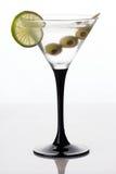 Vetro ed alcool di Martini con le olive verdi Fotografia Stock