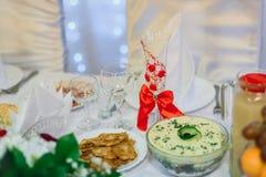 Vetro festivo del champagne decorato con il nastro rosso nel ristorante Fotografie Stock Libere da Diritti