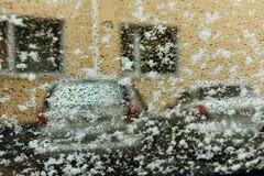 Vetro nelle goccioline ed in neve bagnata, seguite da un'immagine vaga delle automobili e delle costruzioni Fotografia Stock