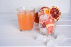 Vetro pieno del succo di pompelmo e vetro di frutta affettata immagini stock