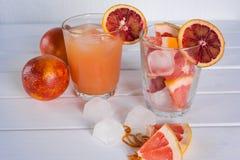 Vetro pieno del succo di pompelmo e vetro di frutta affettata Immagine Stock Libera da Diritti