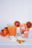 Vetro pieno del succo di pompelmo e vetro di frutta affettata fotografia stock libera da diritti