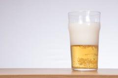 Vetro pieno di bolle e pieno a metà di birra con lo spazio della copia Fotografia Stock