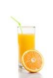 Vetro pieno di succo d'arancia con paglia vicino ad a metà arancio fotografia stock