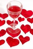 Vetro rosso di vino e cuori rossi Fotografia Stock