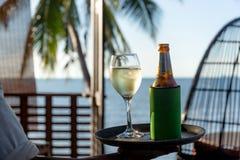 Vetro seaving del cameriere di vino bianco e della bottiglia di birra su un vassoio dalla spiaggia fotografie stock