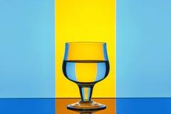 Vetro su un fondo giallo-blu Fotografia Stock