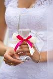 Vetro trasparente di champagne con il nastro rosa cremisi in mani della sposa Immagini Stock