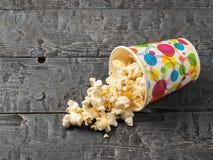 Vetro variopinto invertito di popcorn su una tavola rustica nera fotografia stock