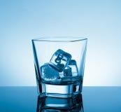 Vetro vuoto di whiskey sulla tavola nera con la riflessione e sul ghiaccio sul fondo blu-chiaro della tinta Immagine Stock