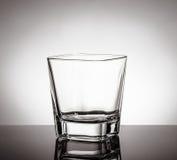 Vetro vuoto di whiskey sulla tavola nera con la riflessione su fondo bianco Fotografia Stock