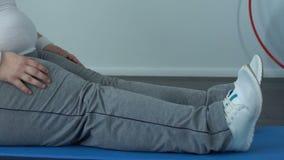 Vette buikpersoon het uitrekken zich benen die mat zitten, die tenen, flexibiliteit proberen te bereiken stock video