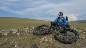 Vette fiets of fatbike of vet-bandfiets in de zomer het drijven door de heuvels stock video