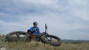 Vette fiets of fatbike of vet-bandfiets in de zomer het drijven door de heuvels stock videobeelden