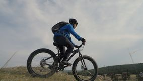 Vette fiets of fatbike of vet-bandfiets in de zomer het drijven door de heuvels stock footage