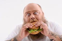 Vette kerel die ongezond voedsel eten royalty-vrije stock fotografie