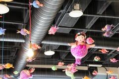 Vette meerminnen die van het dak hangen Stock Foto