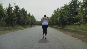 Vette meisjeslooppas langs de weg stock videobeelden