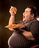 Vette mens die de pizza van de snel voedselplak eten Ontbijt voor te zware persoon Royalty-vrije Stock Fotografie